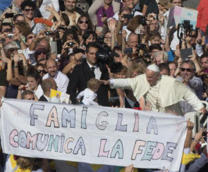 """Pope Francis is driven past a banner reading """"Family communicates faith"""" as he leaves St. Peter's Square at the Vatican, Sunday, Oct.27, 2013. Pope Francis led a Mass on the occasion of the meeting with families. (AP Photo/Alessandra Tarantino)"""